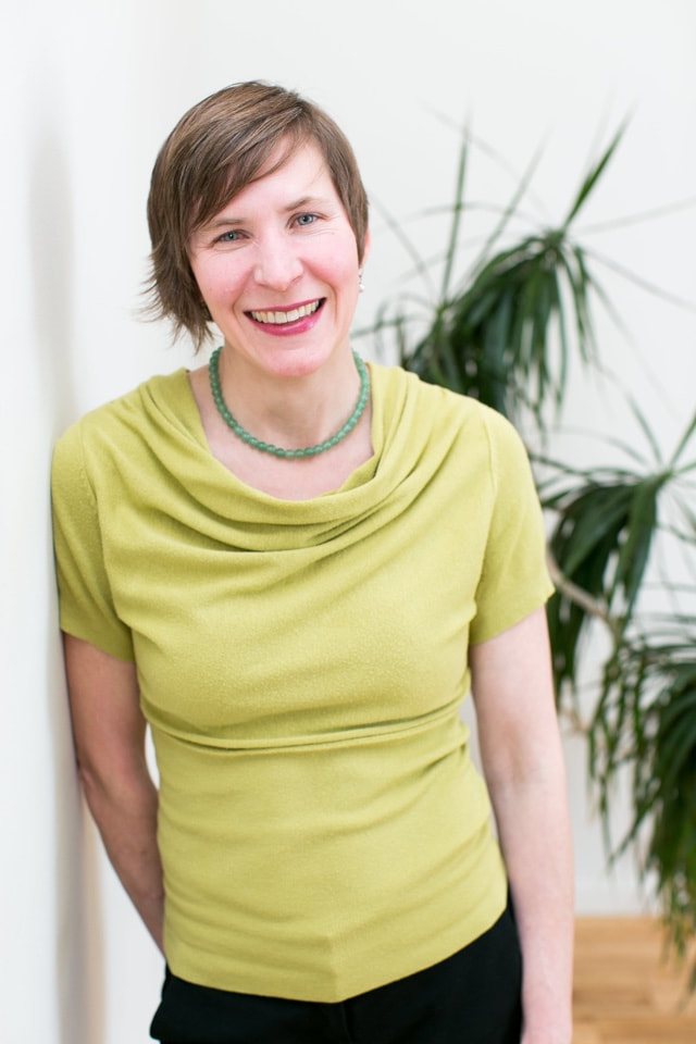 Lynn Salmon-Easter, a white cis-female with light brown hair, smiling, wearing a green shirt with a plant behind her.