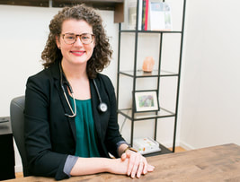 Dr. Barrett, a white cis-female with brown curly hair, smiling. She wears dark, heavy glasses and a turquoise shirt with a black blazer. She is seated at a desk.