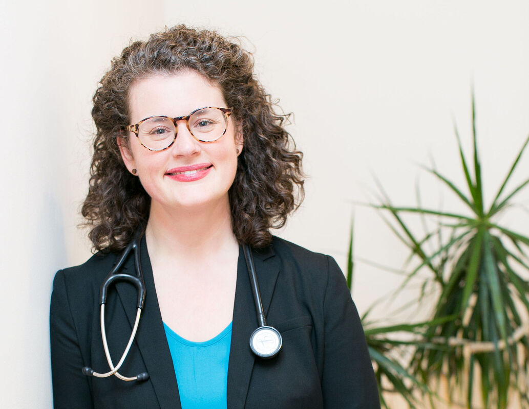Dr. Barrett, a white cis-female with brown curly hair, smiling. She wears dark, heavy glasses and a turquoise shirt with a black blazer.